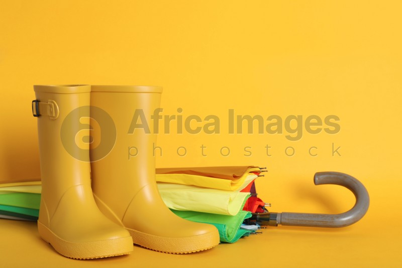 Pair of bright rubber boots near umbrella on pale orange background