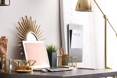 Modern workplace with laptop and golden decor on desk near wall. Stylish interior design