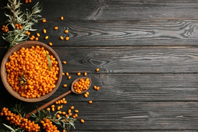 Ripe sea buckthorn berries on black wooden table, flat lay. Space for text
