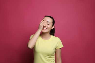 Beautiful young woman laughing on maroon background. Funny joke