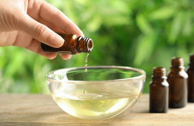 Woman pouring essential oil from glass bottle into bowl on table, closeup