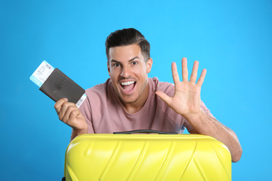 Excited man with suitcase and ticket in passport for summer trip on blue background. Vacation travel