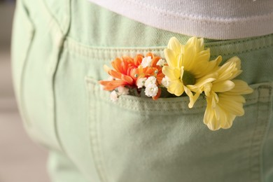 Woman with beautiful tender flowers in light green jeans pocket, closeup