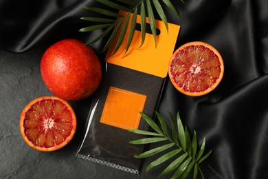 Scented sachet, red oranges and leaves on black table, flat lay