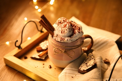 Tasty hot drink with whipped cream and cookies on  wooden table, closeup