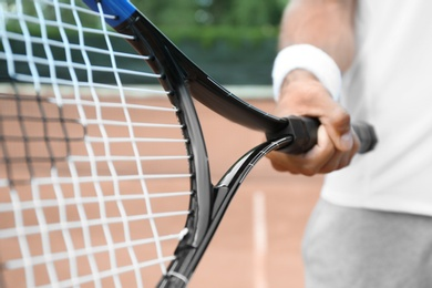 Sportsman with racket at tennis court, closeup