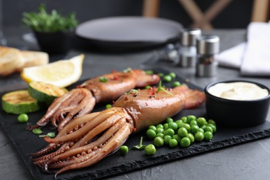 Tasty grilled squids served on black table, closeup