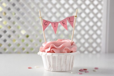 Delicious cupcake with pink cream and Girl topper for baby shower on white table