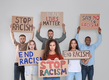 Protesters demonstrating different anti racism slogans on light background. People holding signs with phrases