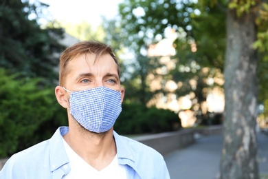 Man wearing handmade cloth mask outdoors, space for text. Personal protective equipment during COVID-19 pandemic
