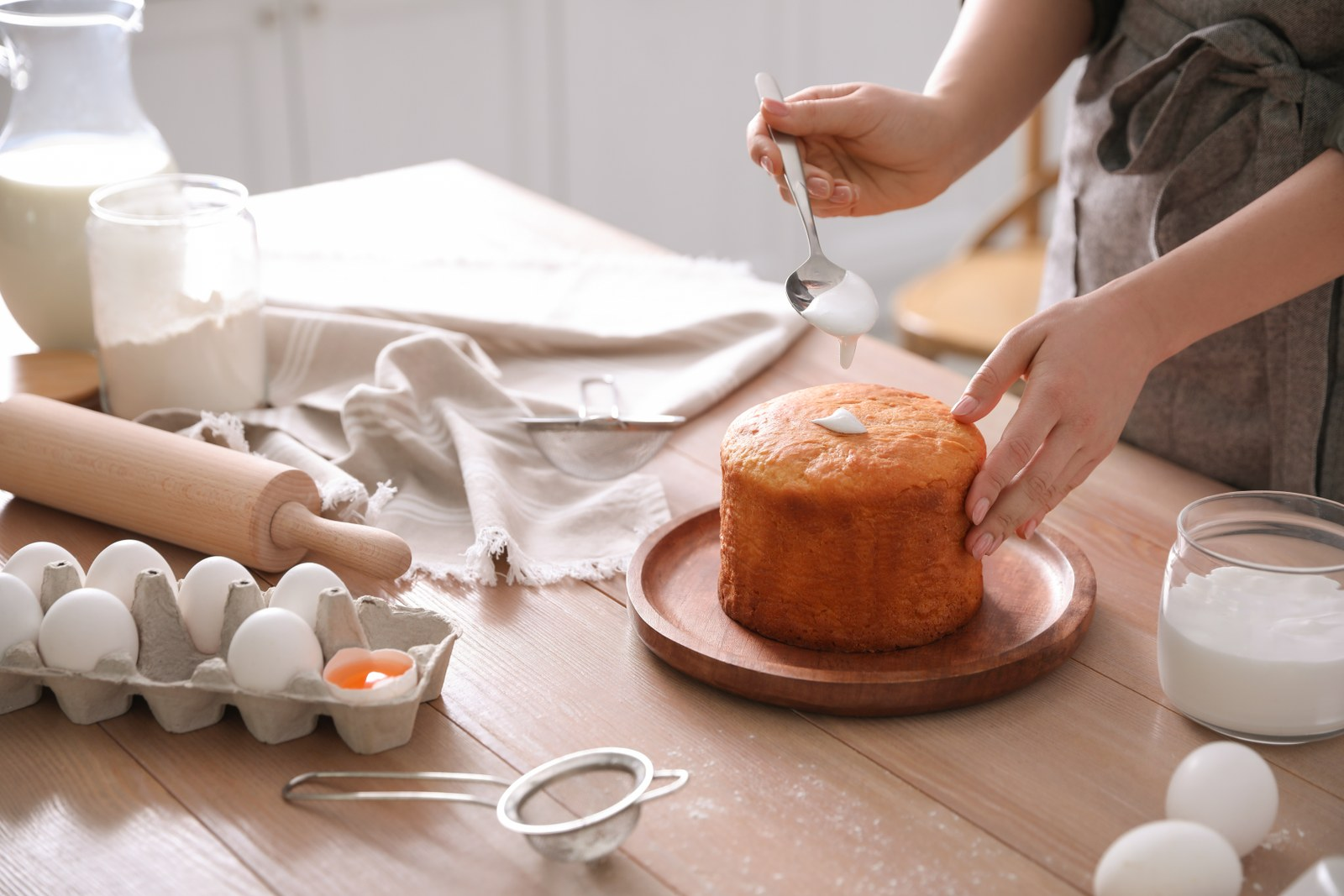 Young woman decorating traditional Easter cake with glaze in kitchen, closeup