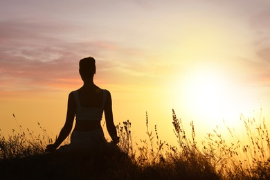 Silhouette of woman meditating outdoors at sunset, back view. Space for text