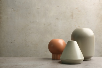 Stylish empty ceramic vases on grey table, space for text