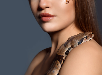 Young woman with boa constrictor on grey background, closeup