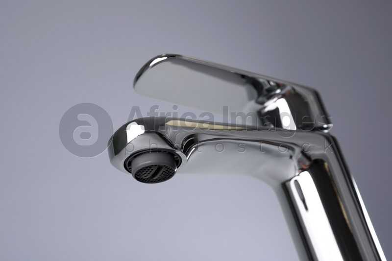 Single handle water tap on grey background, closeup