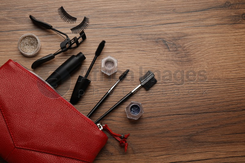 Flat lay composition with eyelash curler, makeup products and accessories on wooden table. Space for text