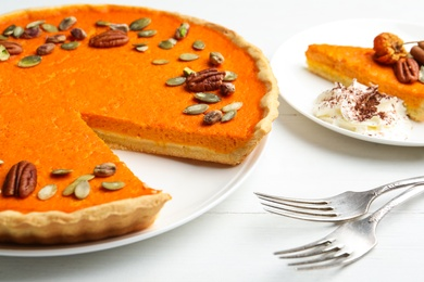Delicious homemade pumpkin pie on white wooden table, closeup