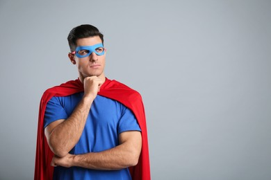 Man wearing superhero cape and mask on grey background. Space for text