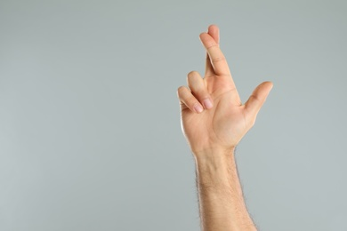 Man with crossed fingers and space for text on grey background, closeup. Superstition concept