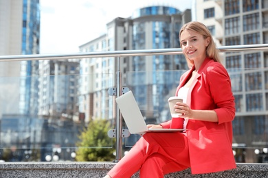 Beautiful businesswoman with laptop and cup of coffee on city street. Space for text