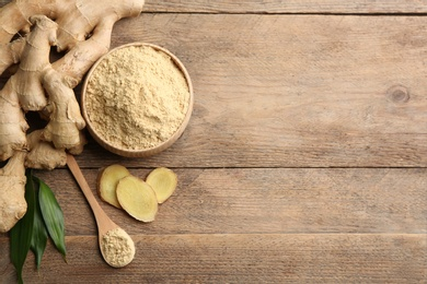 Fresh ginger root, powder and leaves on wooden table, flat lay. Space for text