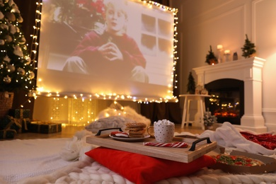MYKOLAIV, UKRAINE - DECEMBER 24, 2020: Video projector screen displaying Home Alone movie in room, focus on tray with snack and drink. Cozy winter holidays atmosphere