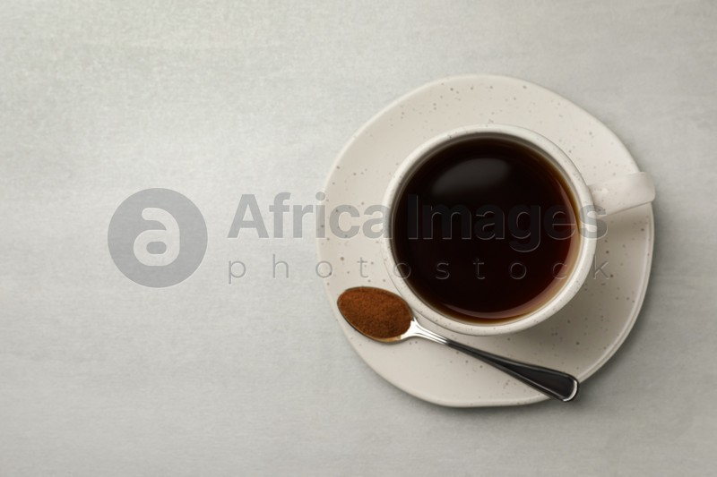 Cup of delicious chicory drink and spoon with powder on light grey table, top view. Space for text
