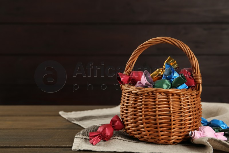 Candies in colorful wrappers on wooden table, space for text