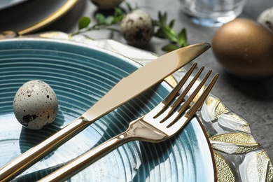 Festive Easter table setting with eggs on color background, closeup
