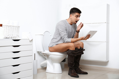 Emotional man with tablet sitting on toilet bowl in bathroom