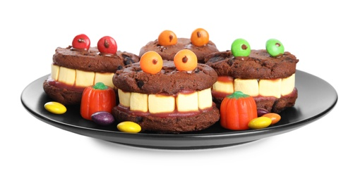 Delicious desserts decorated as monsters on white background. Halloween treat