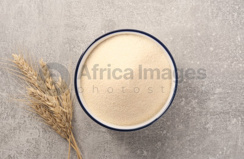 Uncooked organic semolina and spikelets on grey table, flat lay