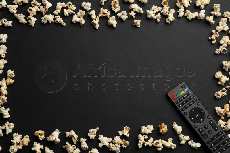 Frame made of popcorn and modern tv remote control on black background, flat lay. Space for text