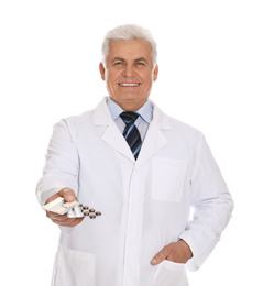 Senior pharmacist with pills on white background