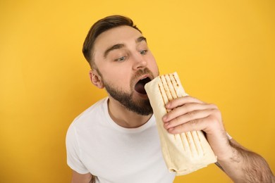 Young man eating delicious shawarma on yellow background