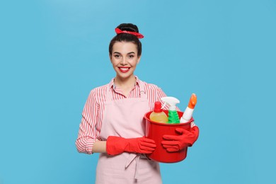Young housewife holding bucket with cleaning supplies on light blue background