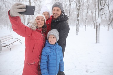Happy family taking selfie outdoors on winter day. Christmas vacation