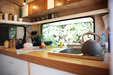 Stylish kitchen interior with different accessories and utensils in modern trailer. Camping vacation