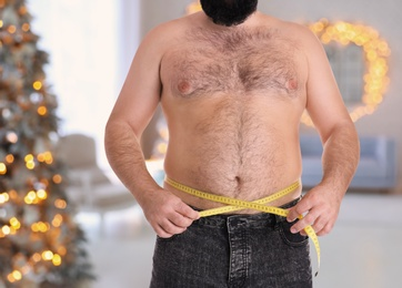 Overweight man measuring his waist in room with Christmas tree after holidays, closeup
