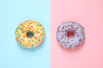 Delicious glazed donuts on color background, flat lay