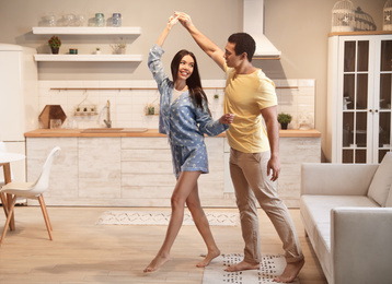 Lovely young interracial couple dancing at home