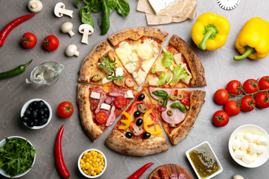 Flat lay composition with slices of different delicious pizzas on grey table