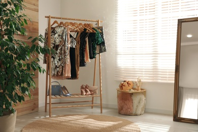 Rack with stylish women's clothes in room. Interior design