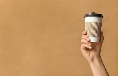 Woman holding takeaway paper coffee cup with cardboard sleeve on brown background, closeup. Space for text