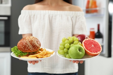 Concept of choice. Woman holding fruits and burger with French fries near refrigerator in kitchen, closeup