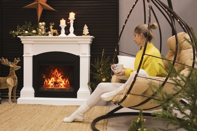 Woman with cup of drink sitting near burning fireplace