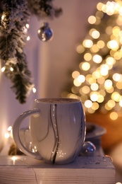 Cup of tasty hot drink and Christmas tree branch indoors. Space for text