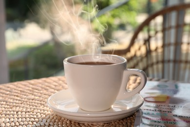 Cup of delicious coffee on rattan table in morning