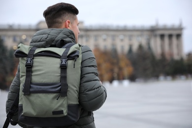 Male tourist with travel backpack on city street, back view. Urban trip