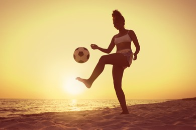 African American woman playing football on beach at sunset